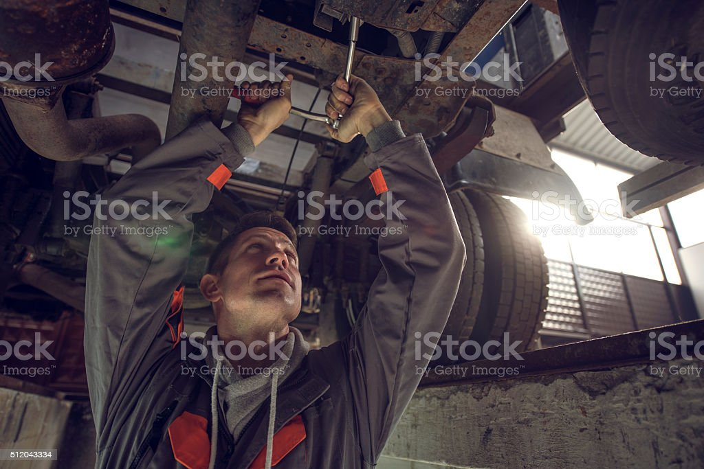 Auto mechanic working on a chassis of a truck. stock photo