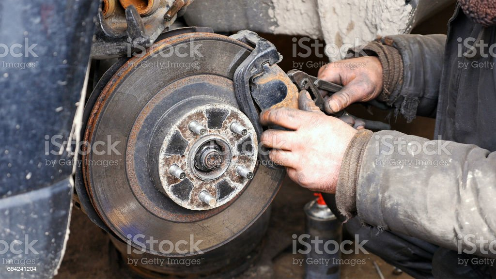 Auto mechanic working on brakes in car repair shop stock photo