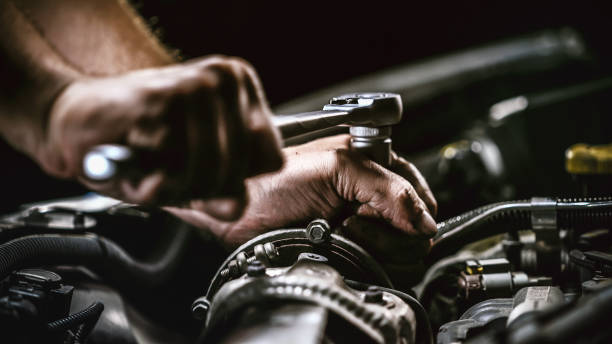 Auto mechanic working on car engine in mechanics garage. Repair service. authentic close-up shot Auto mechanic working on car engine in mechanics garage. Repair service. authentic close-up shot mechanic stock pictures, royalty-free photos & images
