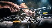 istock Auto mechanic working on car engine in mechanics garage. Repair service. authentic close-up shot 1284285153