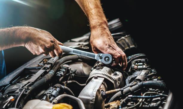 Auto mechanic working on car engine in mechanics garage. Repair service. authentic close-up shot stock photo