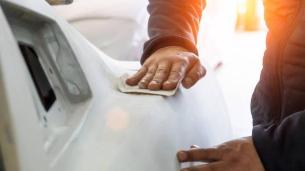 Auto mechanic working on car paint sanding in mechanics garage. workshop repair service. authentic close-up shot. stock photo