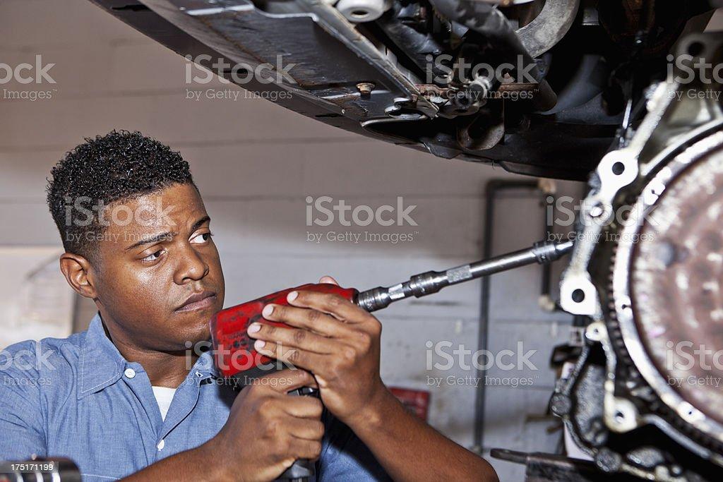 Auto mechanic working on car transmission stock photo