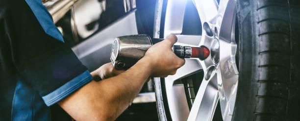 Auto mechanic working on car wheels in mechanics garage. Wheel Tyres Repair service. authentic close-up sho stock photo