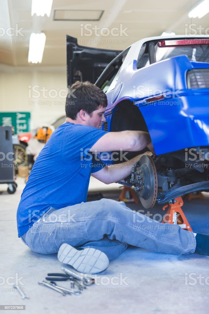 Auto Mechanic Working On Race Car In Home Garage Stock Photo