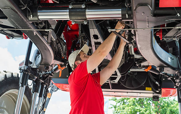 Auto mechanic working Auto mechanic working underneath a lifted agricultural machinery stock pictures, royalty-free photos & images