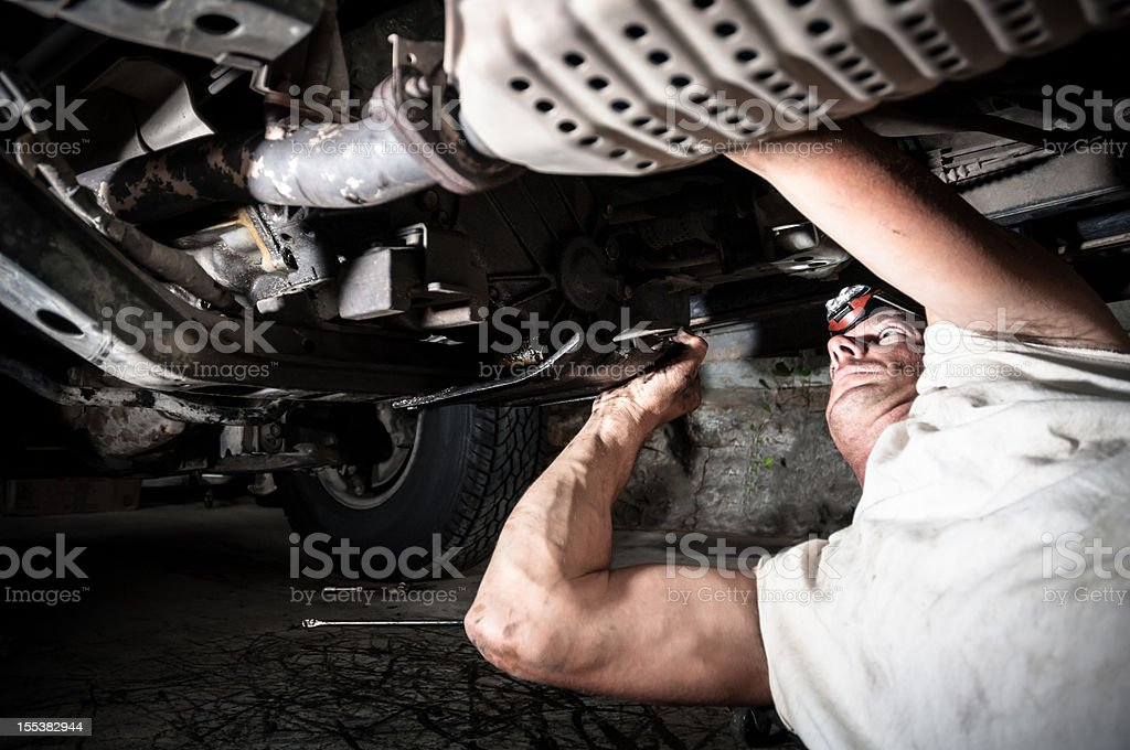 A auto mechanic working under a car stock photo