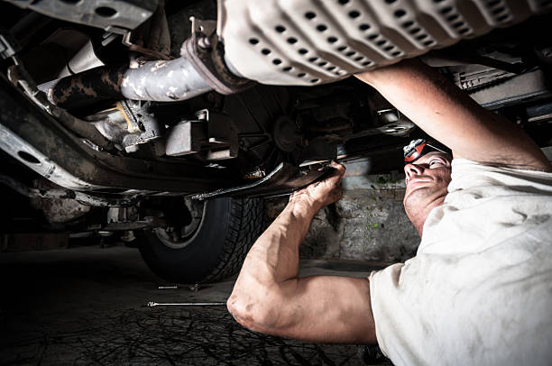 a auto mechanic working under a car - kellyjhall stock pictures, royalty-free photos & images