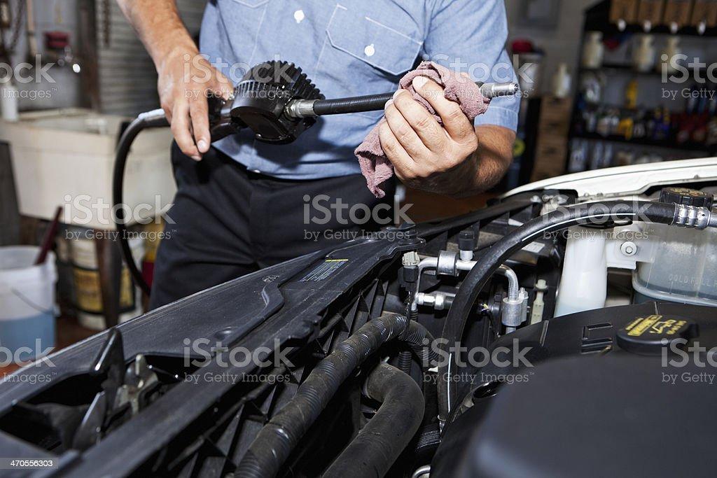 Auto mechanic working under car hood stock photo