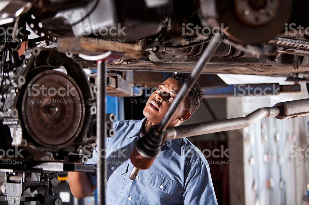Auto mechanic working under raised car stock photo