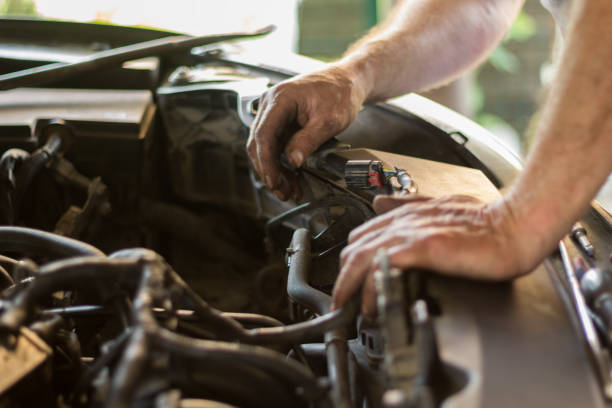 Auto mechanic working under the hood of an old car engine. Auto mechanic working under the hood of an old car engine. vehicle hood stock pictures, royalty-free photos & images