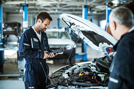 Young mechanic analyzing car's performance with diagnostic tool in a workshop.