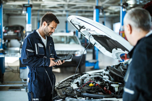 Auto mechanic working with car diagnostic tool in a repair shop. stock photo
