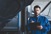 istock Auto mechanic writes on clipboard. Car service concept 1254066380