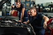 istock Auto mechanics charging car's AC unit in repair shop. 1191771121