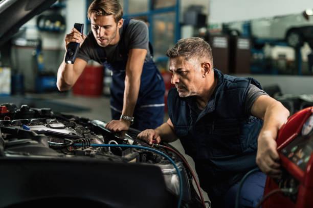 mecánica de automóviles cargando la unidad de ca del coche en el taller de reparación. - compresor motor fotografías e imágenes de stock