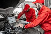 istock Auto mechanics doing diagnostics with laptop 1081594416