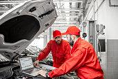 istock Auto mechanics doing diagnostics with laptop 1081594552