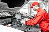 istock Auto mechanics doing diagnostics with laptop 1081594564