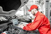 istock Auto mechanics doing diagnostics with laptop 1081594694