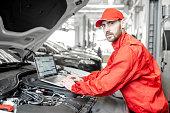 istock Auto mechanics doing diagnostics with laptop 1081594700