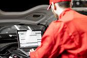 istock Auto mechanics doing diagnostics with laptop 1081594708