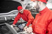 istock Auto mechanics doing diagnostics with laptop 1081595348
