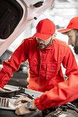 istock Auto mechanics doing diagnostics with laptop 1081595448