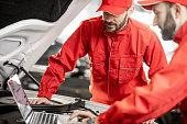 istock Auto mechanics doing diagnostics with laptop 1081595472