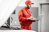 istock Auto mechanics doing diagnostics with laptop 1081595502