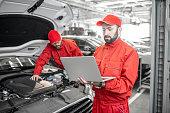 istock Auto mechanics doing diagnostics with laptop 1081595506