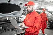 istock Auto mechanics doing diagnostics with laptop 1081595636