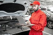 istock Auto mechanics doing diagnostics with laptop 1081595638