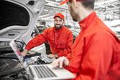 istock Auto mechanics doing diagnostics with laptop 1081595786