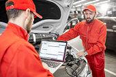 istock Auto mechanics doing diagnostics with laptop 1081595816