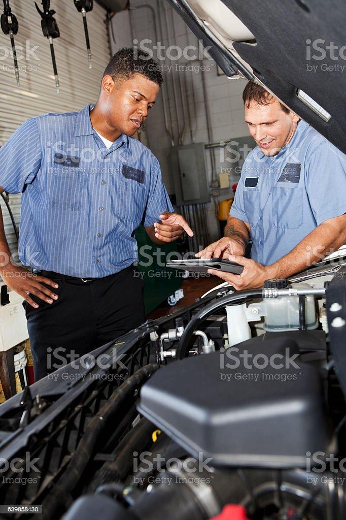 Auto mechanics in garage with digital tablet stock photo