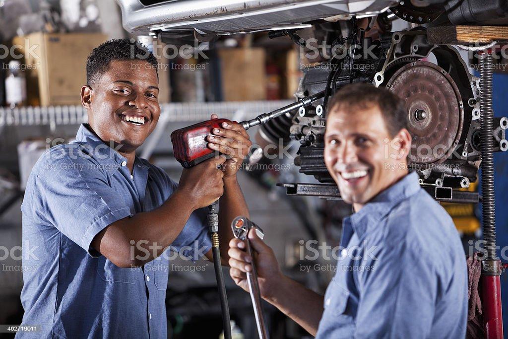 Auto mechanics in garage working on car transmission stock photo