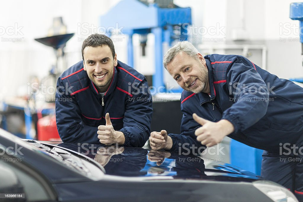 Auto mechanics showing thumbs up royalty-free stock photo