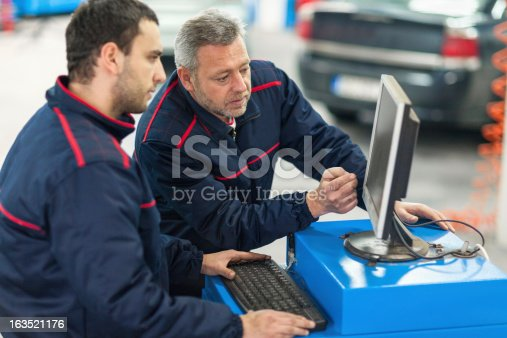 istock Auto mechanics working in repair shop 163521176