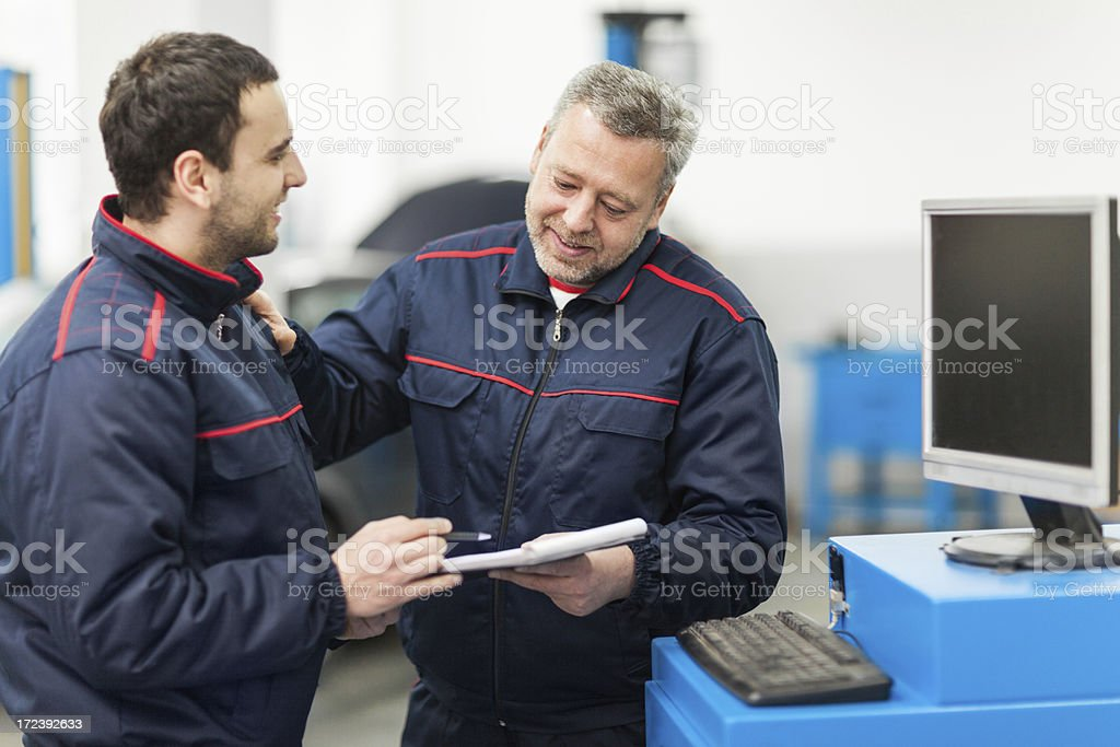 Auto mechanics working in repair shop royalty-free stock photo