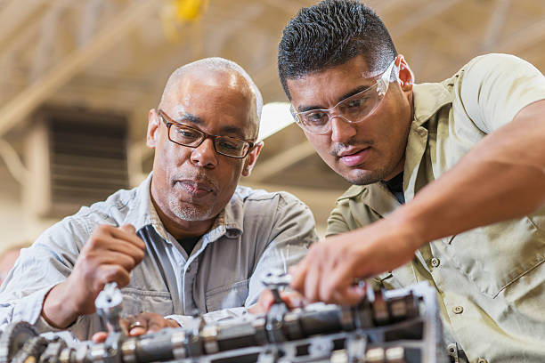 Auto mechanics working on gasoline engine stock photo