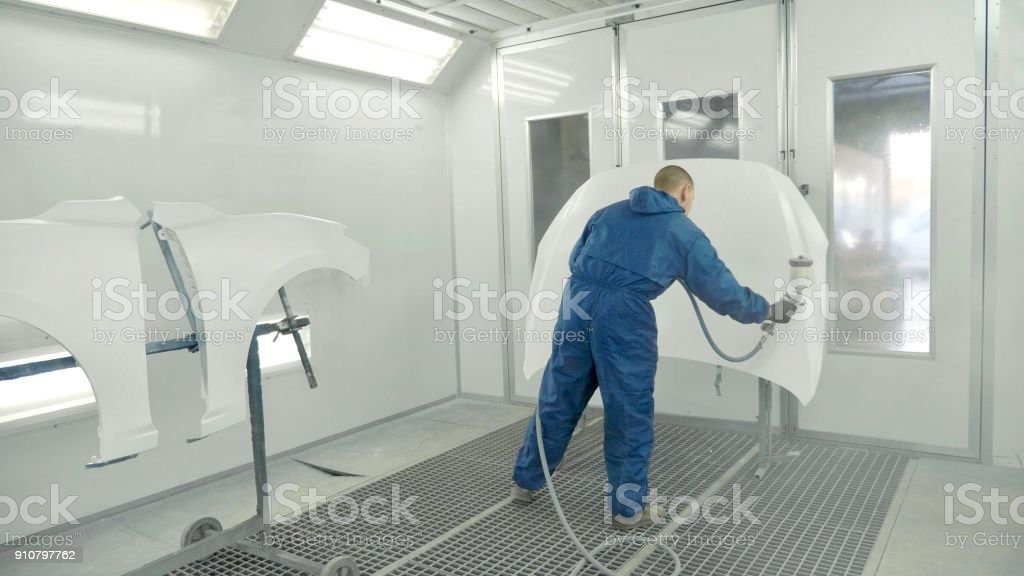 Auto painter spraying white paint on car hood in special booth stock photo