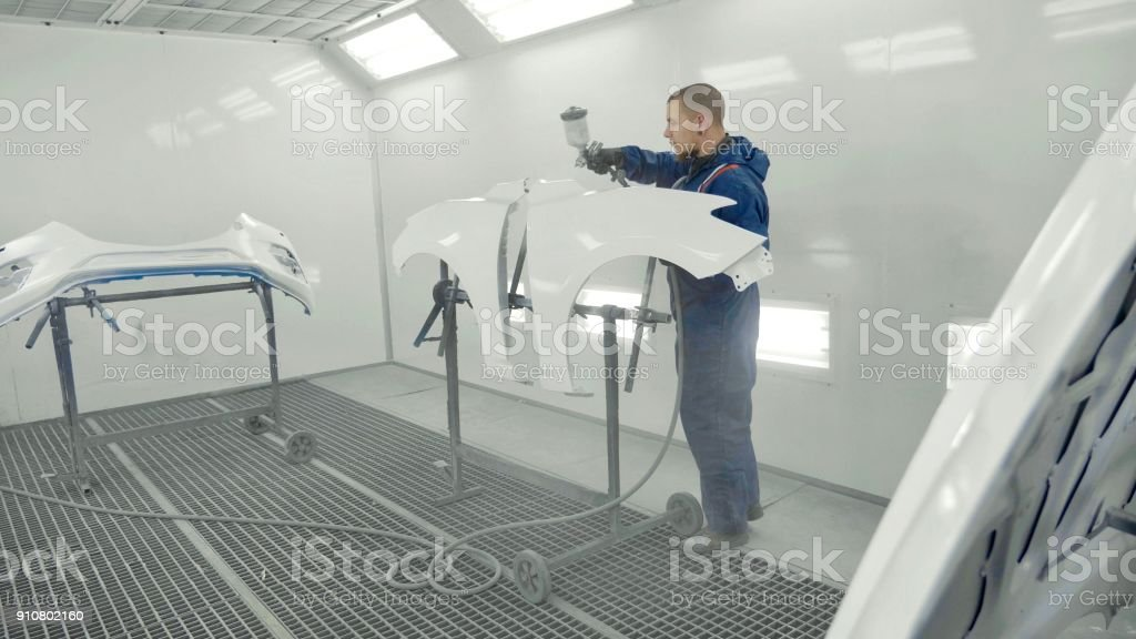 Auto painter spraying white paint on car spare fender in special booth stock photo
