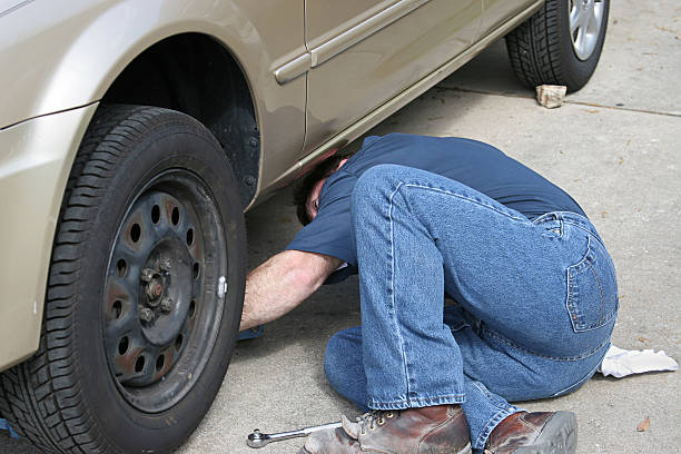 Auto Repair A mechanic reaching under a car.   Photo taken as work was actually being performed. socket wrench stock pictures, royalty-free photos & images