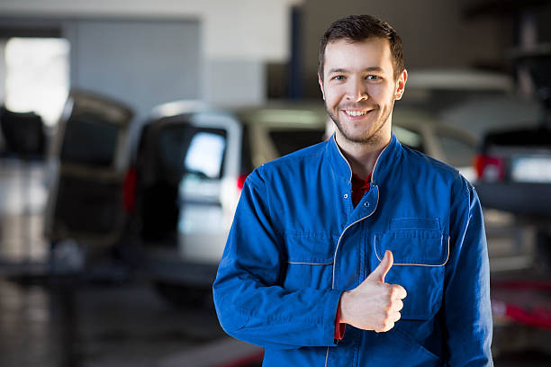 auto repair service. handsome smiling mechanic - auto body repair stock photos and pictures