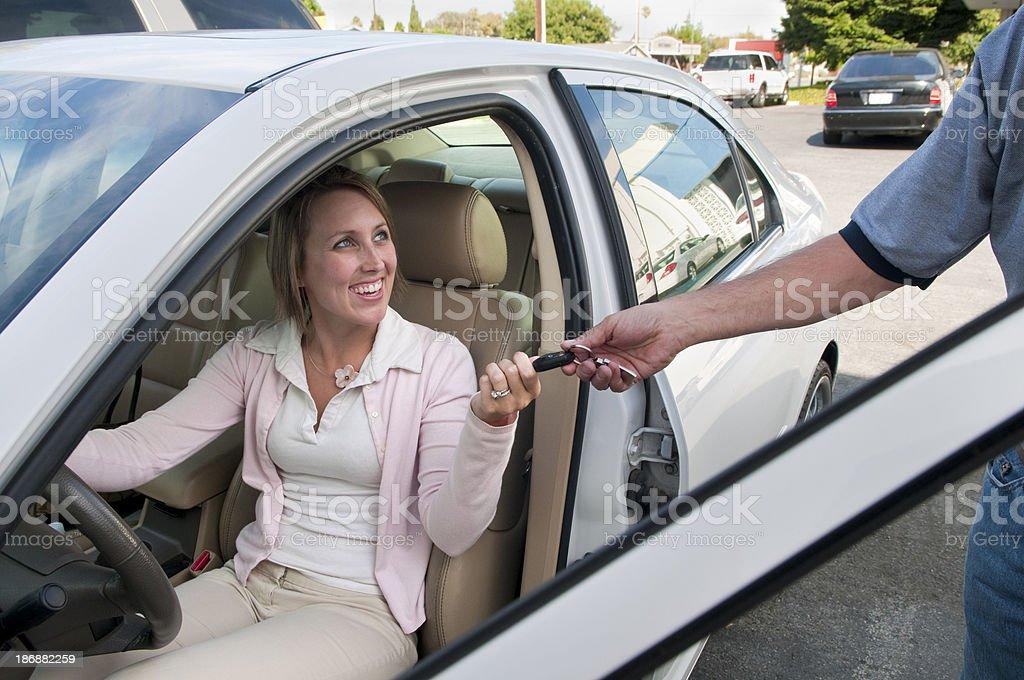 Auto Repair Serviceman Handing Keys to Customer royalty-free stock photo