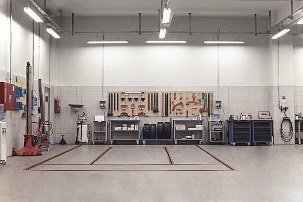 autowerkstatt innenraum mit mechaniker im hintergrund - autowerkstatt stock-fotos und bilder