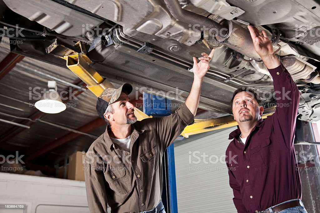 Auto repair shop, looking under vehicle royalty-free stock photo