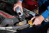 Auto repair shop - mechanic refills radiator anti-freeze