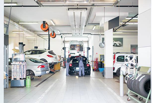garage automobile avec voiture desservi par les mécaniciens - garagiste photos et images de collection